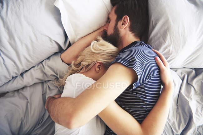 Pareja acostado en la cama juntos, durmiendo, brazos alrededor de la otra - foto de stock