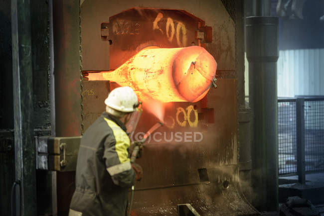 Rear view of steelworker pressure washing forge press — Stock Photo