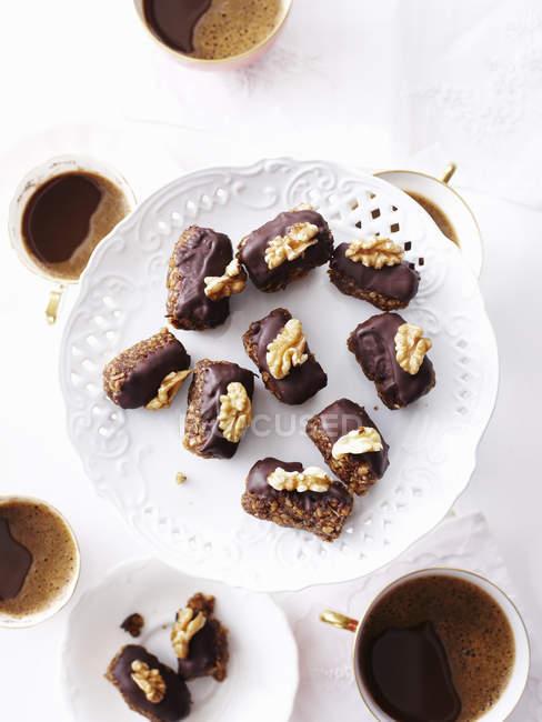 Stillleben aus Schokolade und Walnuss-Macadamia-Kuchen auf Teller — Stockfoto
