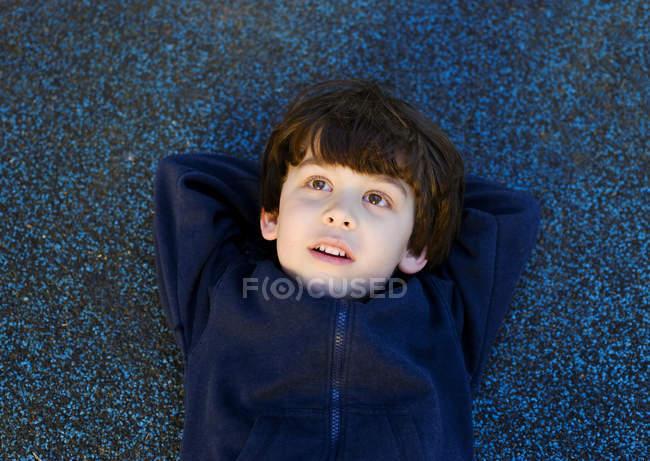 Милый мальчик лежит на спине и смотрит вверх. — стоковое фото