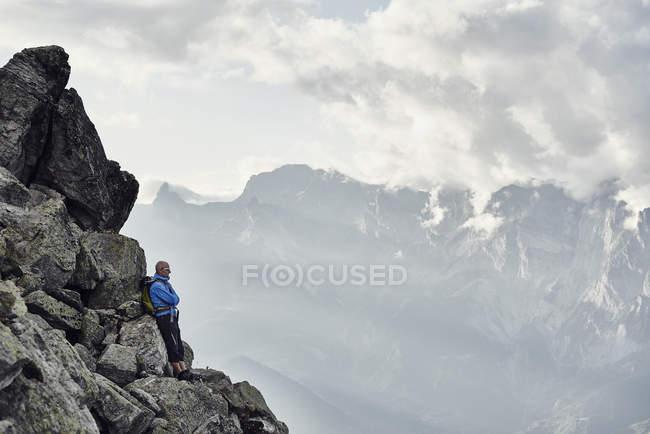 Mature man leaning against rocks, Valais, Switzerland — Stock Photo