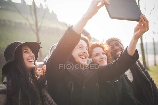 Six jeunes amis adultes prenant selfie tablette numérique dans le parc — Photo de stock
