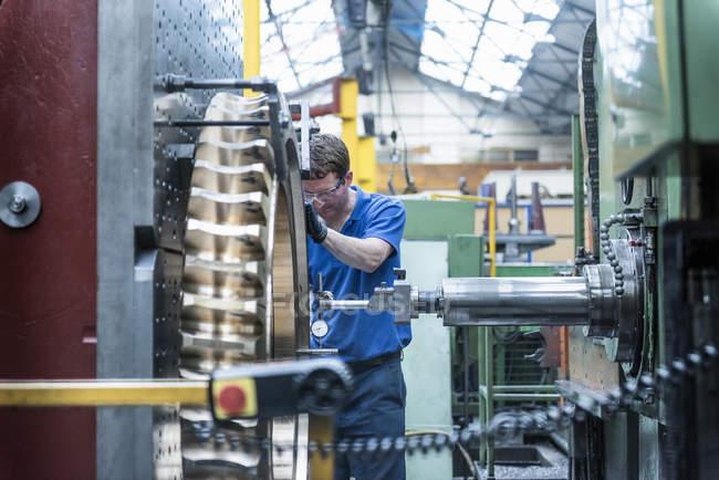 Engineer measuring gear wheel in lathe in engineering factory — Stock Photo