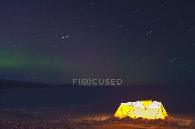 Carpa iluminada y luces en el cielo estrellado del norte - foto de stock