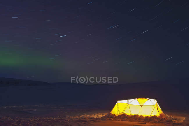 Illuminated tent and northern lights in starry sky — Stock Photo