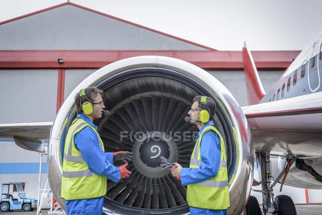 Бортинженеры осматривают реактивный двигатель самолета — стоковое фото
