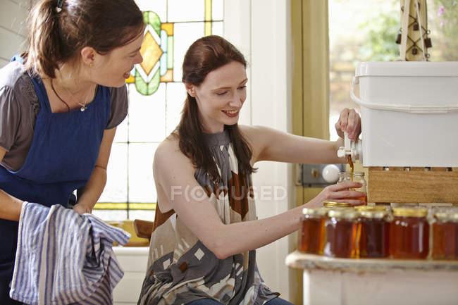Apicultores femininos na cozinha, engarrafamento de mel filtrado da colmeia — Fotografia de Stock
