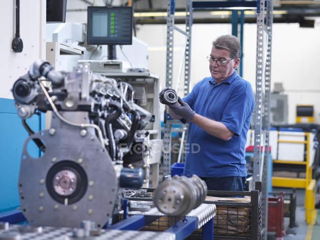 Ingenieur mit Zahnrad und Dieselmotor in Maschinenfabrik — Stockfoto