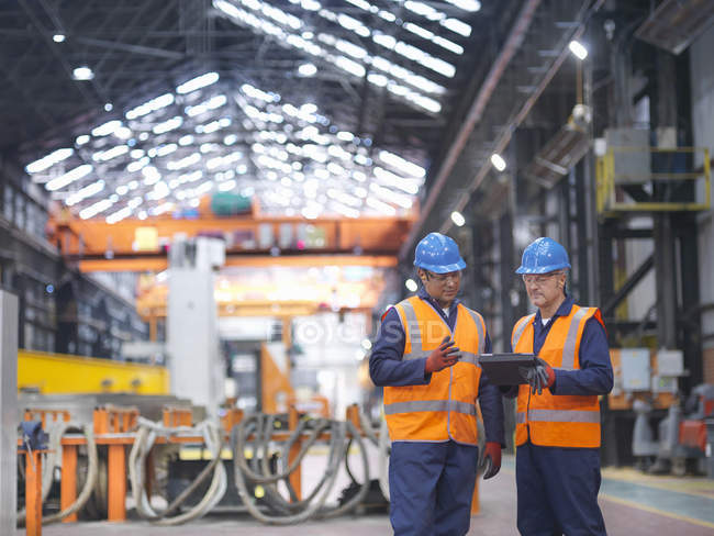 Steelworkers in discussion in engineering factory — Stock Photo