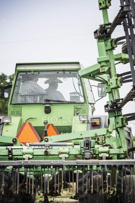 Vue arrière du fermier et petit-fils adolescent, conduite de tracteur agricole — Photo de stock