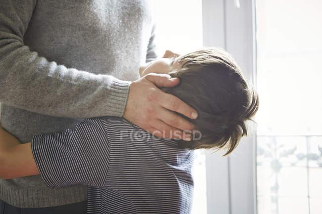 Батько і син обіймаючи вікно в приміщенні, хлопчик дивиться — стокове фото