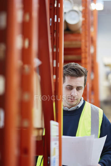 Male factory worker checking paperwork in factory warehouse — Stock Photo