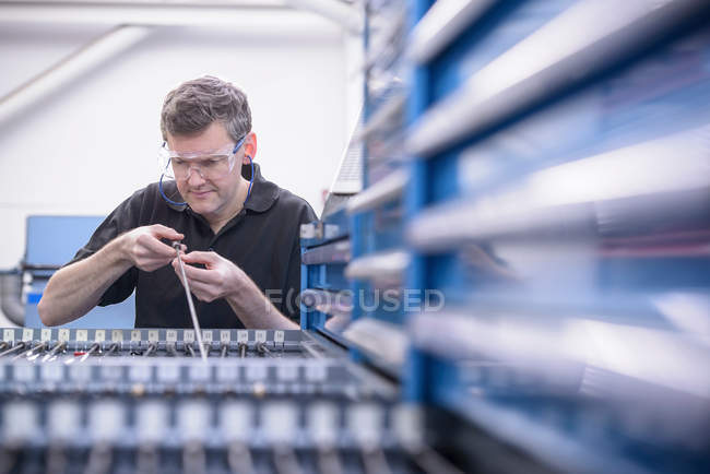 Engineer wearing safety glasses and inspecting drill rods — Stock Photo