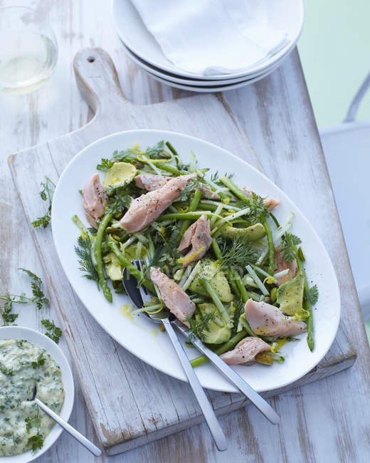 Plate of asparagus, avocado and dill salad with trout — Stock Photo