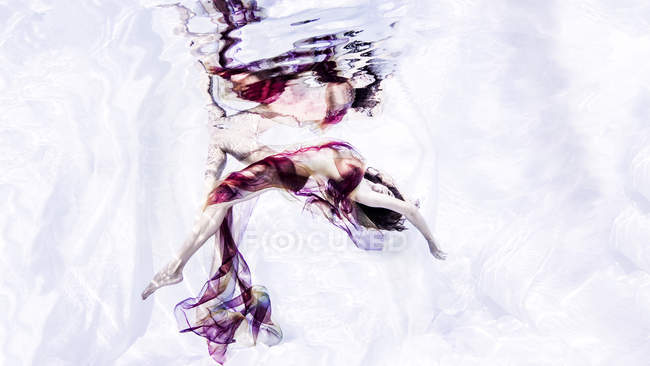 Underwater view of woman draped in sheer fabric, bending backwards — Stock Photo