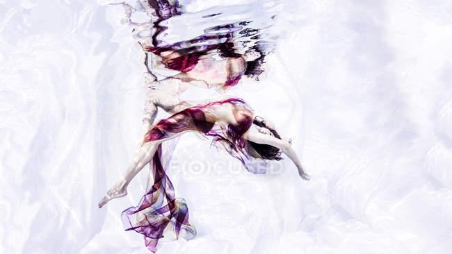 Vue sous-marine de la femme drapée dans un tissu pur, se penchant vers l'arrière — Photo de stock
