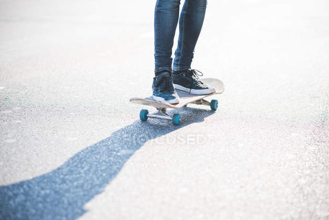 Legs of male urban skateboarder swerve skateboarding on road — Stock Photo