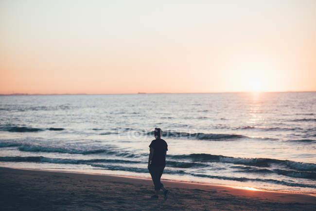 Femme se promenant sur la plage au coucher du soleil, Sorso, Sassari, Italie — Photo de stock