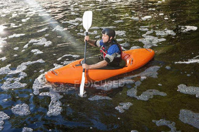Средний взрослый мужчина, каякинг на мирное река — стоковое фото