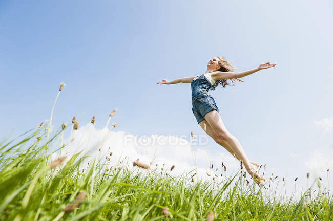 Woman jumping in midair with arms open — Stock Photo