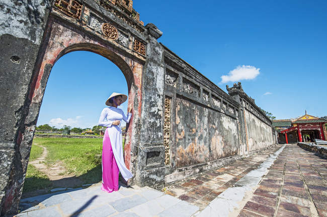Mid adult woman standing in archway of imperial palace wearing ao dai and conical hat, Hue, Vietnam — Stock Photo