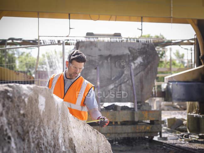 Travailleur de carrière mesurant les roches devant la scie à pierre — Photo de stock