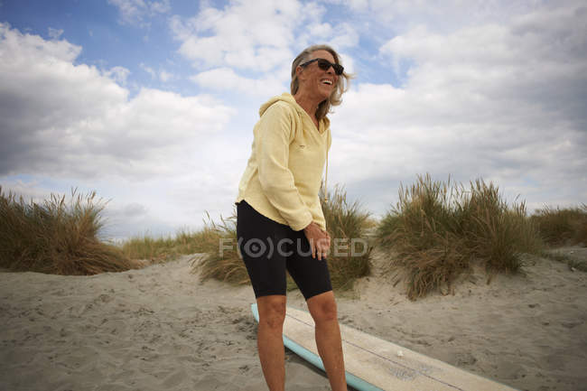 Senior woman putting on wetsuit — Stock Photo