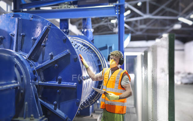 Worker checking metal ore grinding mill equipment — Stockfoto
