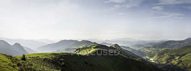 Panoramic landscape of green hills in sunlight — Stock Photo