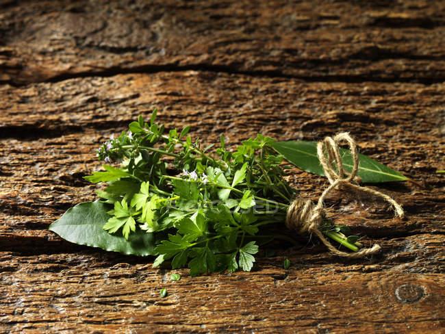 Persil, thym, feuilles de Laurier attachés ensemble avec string sur une surface en bois rustique — Photo de stock