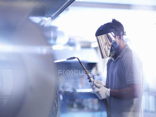 Ventilateur en verre apprenti portant un masque et utilisant une lance — Photo de stock