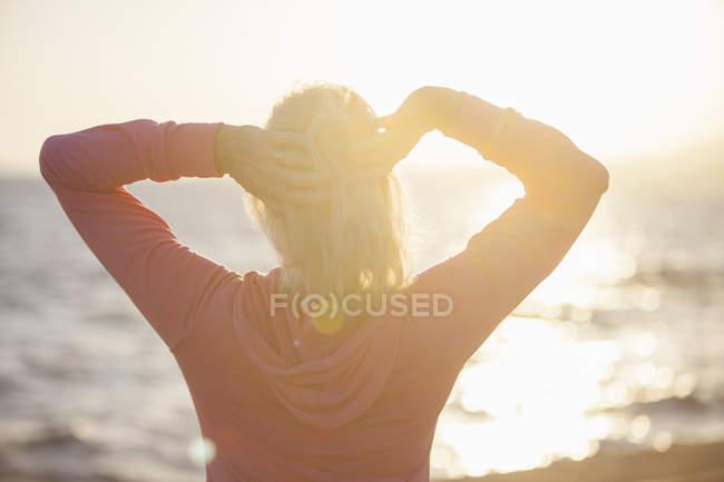Mulher sênior alongamento por praia — Fotografia de Stock