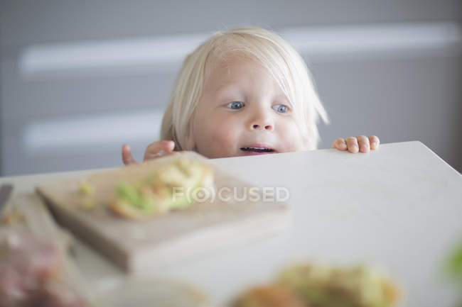 Neugier junge peeking über Küchentheke — Stockfoto