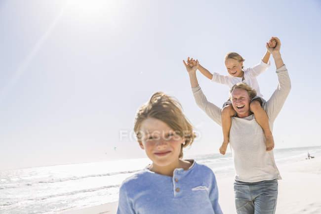 Père et fils sur la plage, portant sur les épaules souriant — Photo de stock