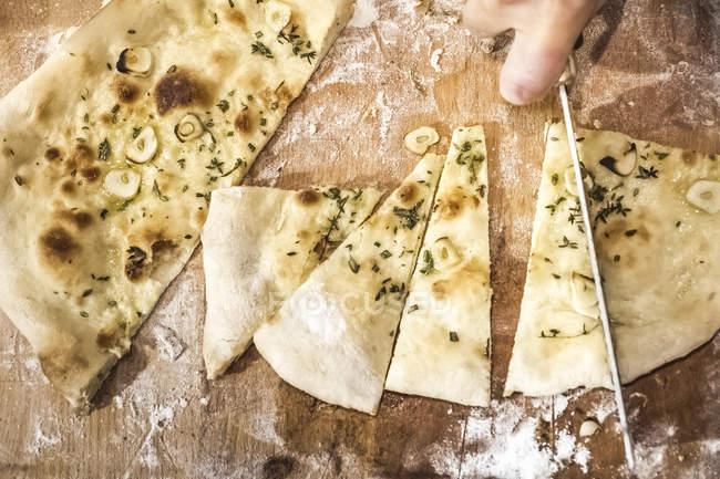 Cropped image du chef, découper la pâte à pizza dans la cuisine commerciale — Photo de stock