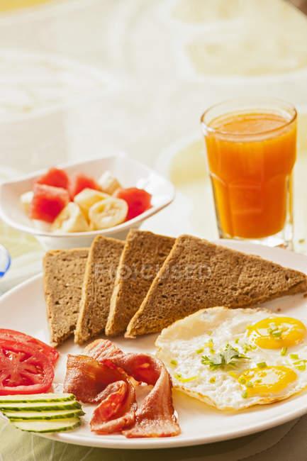 Смажені яйця та бекон сніданок з хліб з непросіяного борошна, фруктовий салат й апельсиновий сік — стокове фото