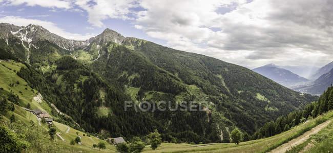 Vue grand angle de collines verdoyantes sous ciel nuageux — Photo de stock