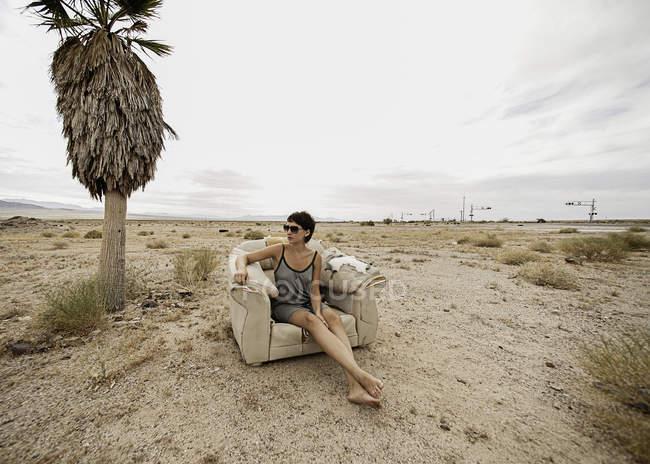 Jeune femme relaxante dans un fauteuil dans le désert — Photo de stock