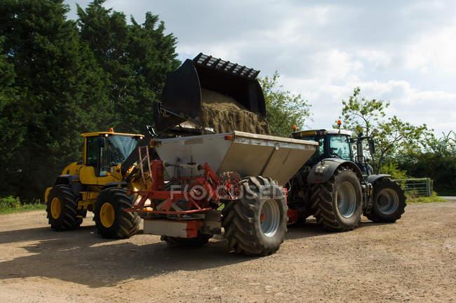 Фермер передачі органічних добрив в добрива розкидач у Фермерське подвір'я — стокове фото