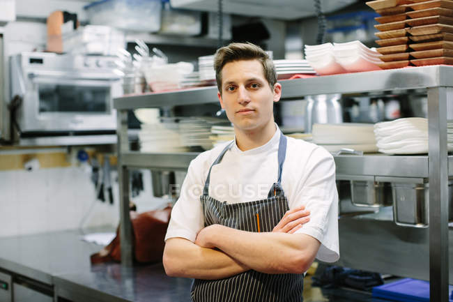 Portrait of young male chef with arms folded in kitchen — Stock Photo