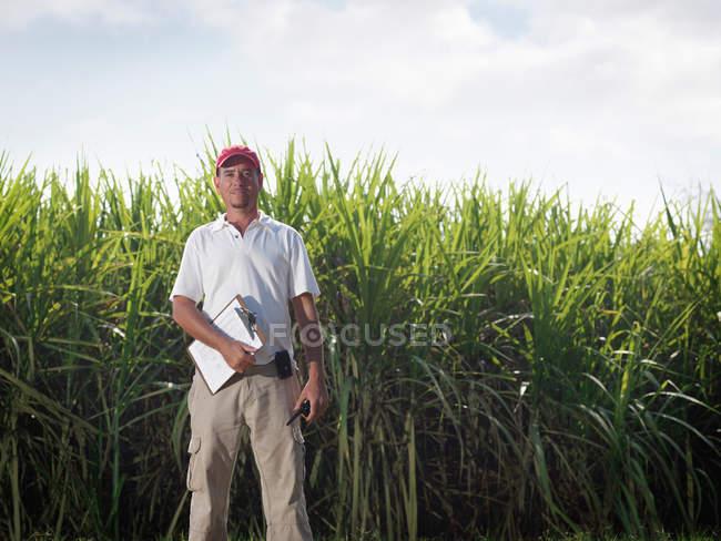 Supervisor com placa de grampo e cana de açúcar — Fotografia de Stock