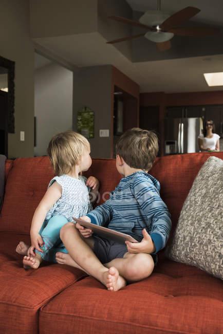 Брати і сестри обертаючись від цифрової планшета на дивані вдома — стокове фото