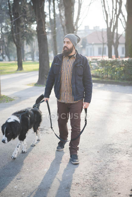 Mid adult man walking dog through park — Stock Photo