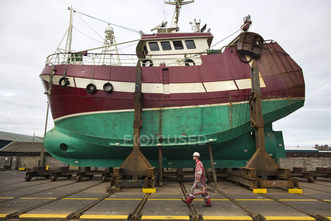 Male ship painter walking in front of fishing boat on drydock — Stock Photo