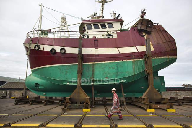 Pintor de nave hombre camina delante de barco de pesca en el dique seco - foto de stock