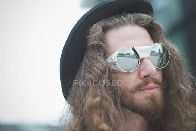 Close up of young male hippy with long hair and sunglasses — Stock Photo