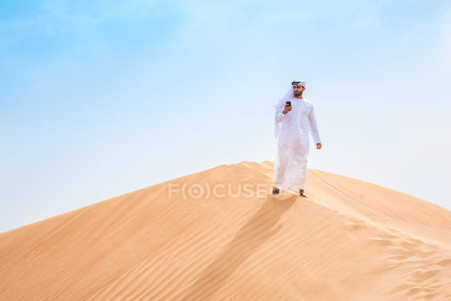 Middle eastern man wearing traditional clothes using smartphone on desert dune, Dubai, United Arab Emirates — Stock Photo