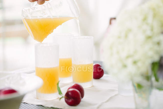 Woman pouring orange juice into glass — Stock Photo