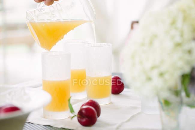Donna versando il succo d'arancia nel bicchiere — Foto stock