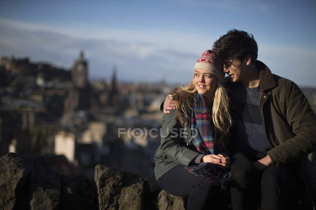 A young couple hug on Calton Hill with the background of the city of Edinburgh, capital of Scotland — Stock Photo